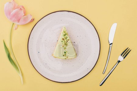 top view of piece of cake on plate, tulip flower and cutlery isolated on yellow
