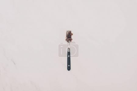top view of fork with cake pieces isolated on grey