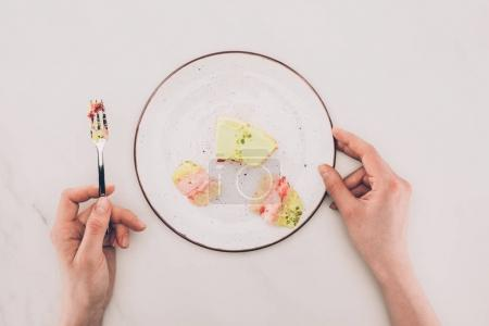 partial view of female hands and pieces of cake on plate on white surface