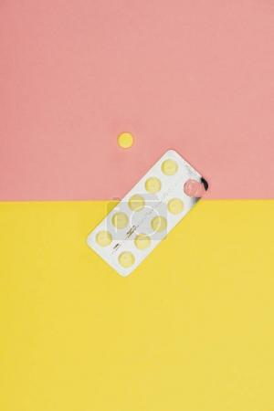 Photo pour Vue du dessus des pilules isolées sur fond rose et jaune - image libre de droit