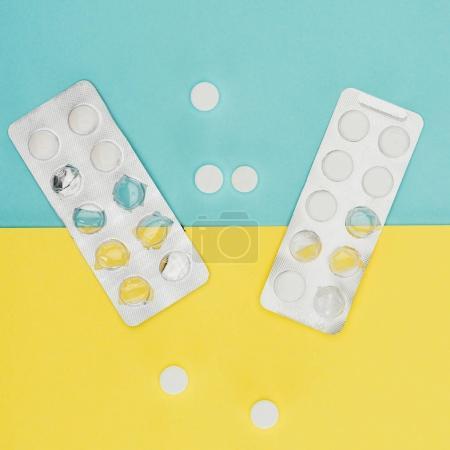Photo pour Vue du dessus des médicaments isolés sur fond bleu et jaune - image libre de droit
