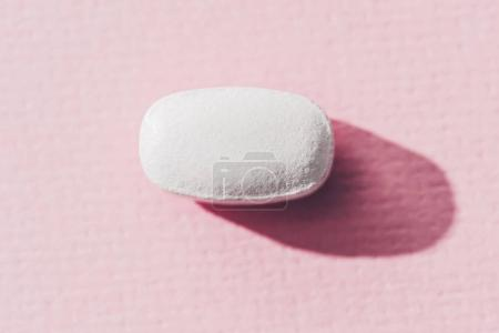 close up view of medicine on pink surface