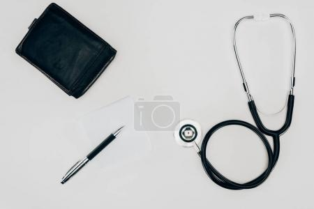 top view of medical stethoscope, wallet and pen on white surface
