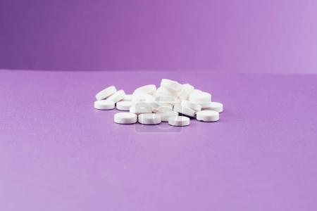 Nahaufnahme von arrangierten Pillen auf violettem Hintergrund