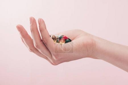 partial view of woman holding pills in hand isolated on pink