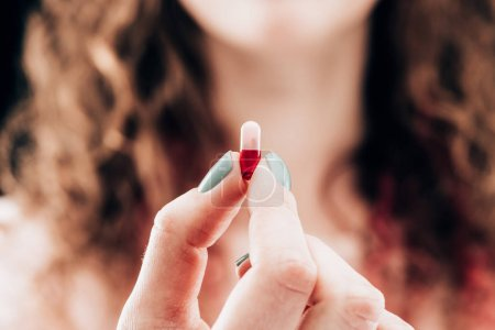partial view of woman showing pill in hand