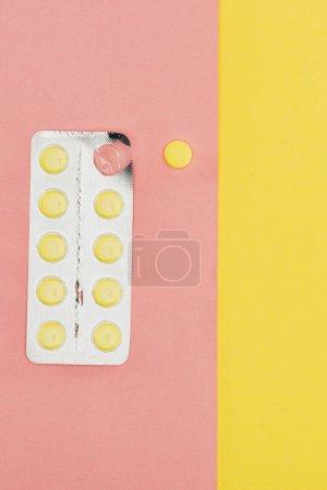 top view of pills isolated on pink and yellow background