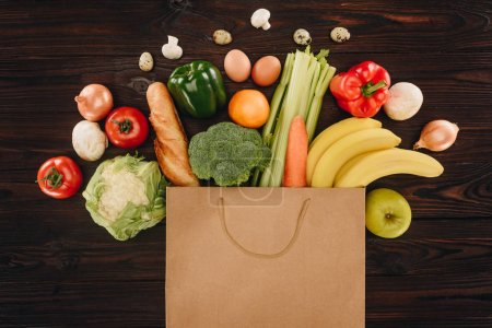 top view of different vegetables and fruits in paper bag on wooden table, grocery concept