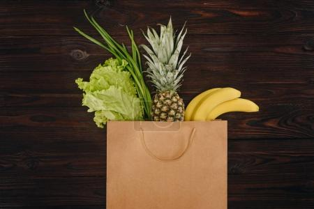 top view of chinese cabbage, pineapple and bananas in shopping bag on wooden table