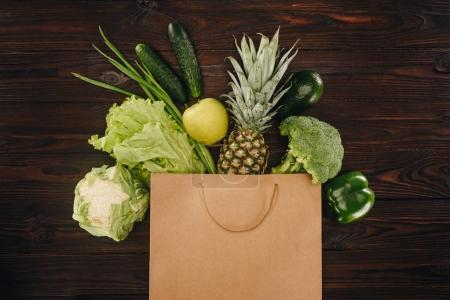 top view of green vegetables and fruits in shopping bag on wooden table