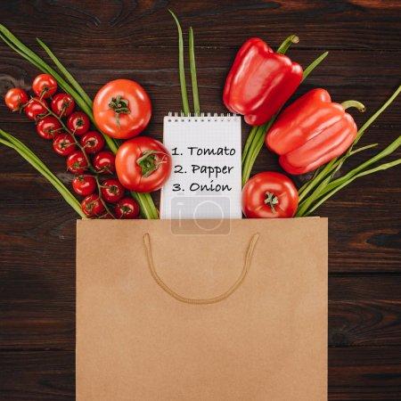 Foto de Vista superior de verduras y notebook con nota en mesa de madera, concepto de tienda de comestibles - Imagen libre de derechos
