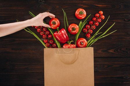cropped image of girl taking tomato from shopping bag