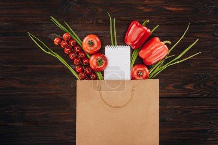 Foto de Vista superior de los tomates rojos y pimientos con cuaderno vacío en mesa de madera, concepto de tienda de comestibles - Imagen libre de derechos