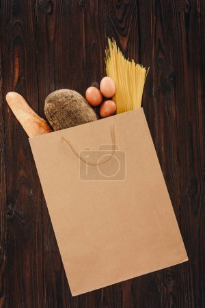 top view of bread, pasta and eggs in shopping bag on wooden table, grocery concept