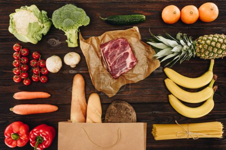 top view of raw meat with vegetables, fruits and bread on wooden table, grocery concept
