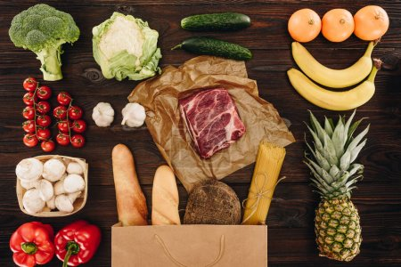 top view of raw meat with vegetables and fruits on wooden table, grocery concept