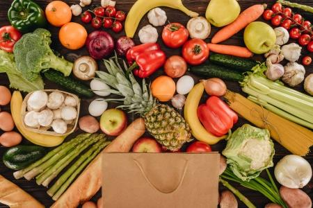 top view of shopping bag with vegetables and fruits on wooden table