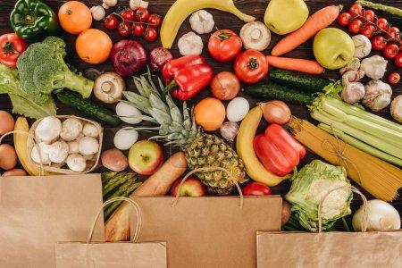 Photo pour Vue de dessus des sacs en papier couvrant les légumes et les fruits sur la table en bois, concept d'épicerie - image libre de droit