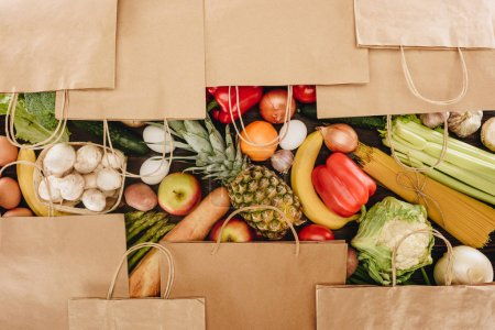 Photo for Top view of shopping bags covering vegetables and fruits on wooden table - Royalty Free Image