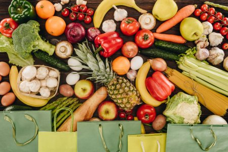 Photo for Top view of vegetables and fruits with paper bags on wooden table - Royalty Free Image