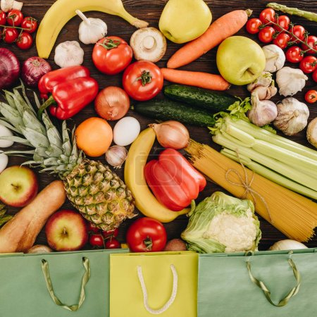 Photo for Top view of vegetables with fruits and shopping bags on wooden table, grocery concept - Royalty Free Image
