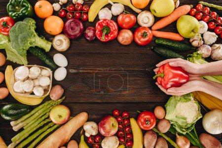 Photo pour Image recadrée de fille tenant poivron au-dessus des légumes et fruits sur table en bois - image libre de droit