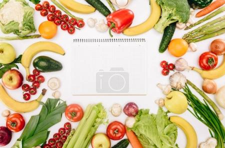 top view of empty notebook between vegetables and fruits isolated on white, grocery concept