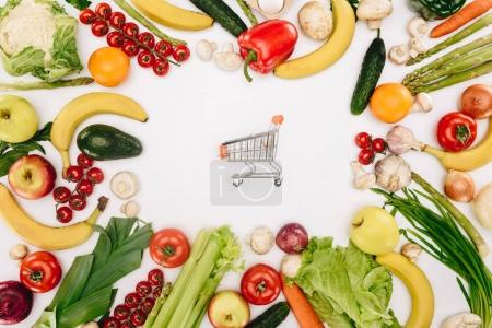 top view of shopping cart between vegetables and fruits isolated on white, grocery concept