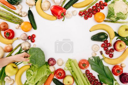 Photo for Cropped image of girl taking broccoli from table with vegetables and fruits isolated on white - Royalty Free Image