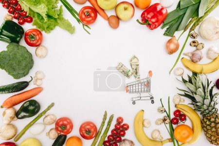 top view of small shopping cart with dollars between vegetables and fruits isolated on white