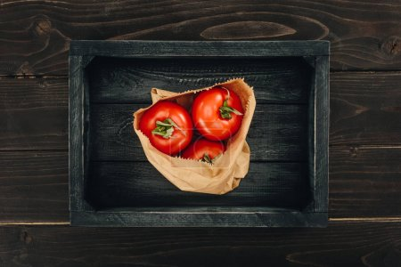 top view of red tomatoes in shopping paper bag