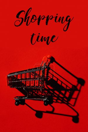 one shopping cart with shadow on red wall and words Shopping time