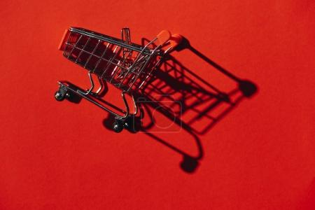 one shopping cart with shadow on red wall
