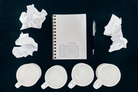 top view of blank notepad with crumpled papers and empty cups in row isolated on black