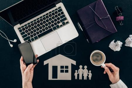 cropped shot of family lawyer using smartphone at workplace with house and family cut out figures isolated on black