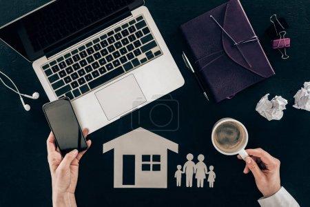 Photo pour Recadrée tir d'avocat de la famille à l'aide de smartphone sur lieu de travail avec la famille et la maison Découpez chiffres isolés sur fond noir - image libre de droit