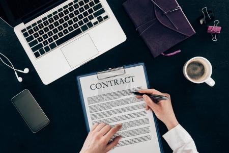 Photo pour Photo recadrée de femme d'affaires, signature du contrat au lieu de travail isolé sur fond noir - image libre de droit