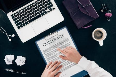 Photo pour Photo recadrée de femme lisant le contrat sur le lieu de travail isolé sur fond noir - image libre de droit