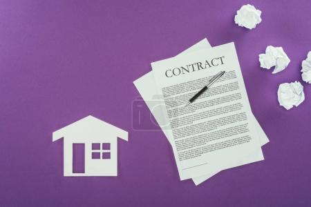 top view of business contract with pen and house symbol on purple surface