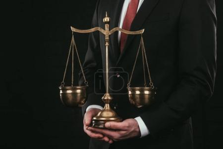 cropped shot of lawyer holding themis scales isolated on black