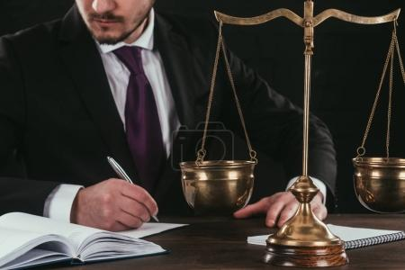 cropped shot of lawyer doing paperwork at workplace with scales isolated on black