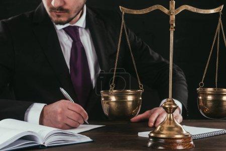 Photo pour Recadrée tir d'avocat, faire de la paperasse sur lieu de travail avec des écailles isolées sur fond noir - image libre de droit