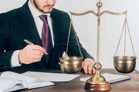 cropped shot of lawyer doing paperwork at workplace with scales
