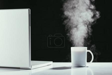 laptop with steaming cup of tea on table isolated on black