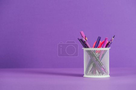 pen holder with various pens and pencils on purple surface