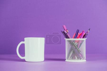 Photo for Cup and pen holder on purple surface - Royalty Free Image