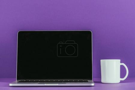 Photo for Business workplace with laptop and coffee mug on purple surface - Royalty Free Image