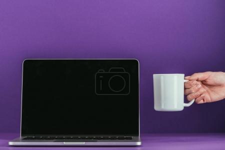 Photo pour Recadrée tir de femme mug golding de café près de portable sur une surface pourpre - image libre de droit