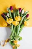 """Постер, картина, фотообои """"вид сверху желтые, розовые и белые тюльпаны с лентой на Международный женский день"""""""