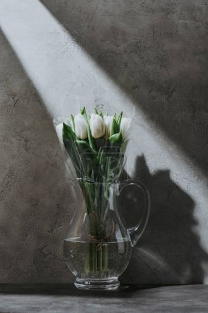 white spring tulips in glass jug on grey concrete surface with shadow